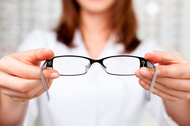 Woman holding out pair of glasses