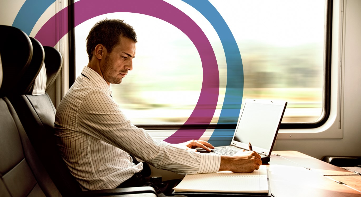 Man sitting at a table on a train working on his laptop