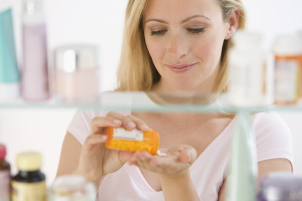 Woman looks in her medicine cabinet