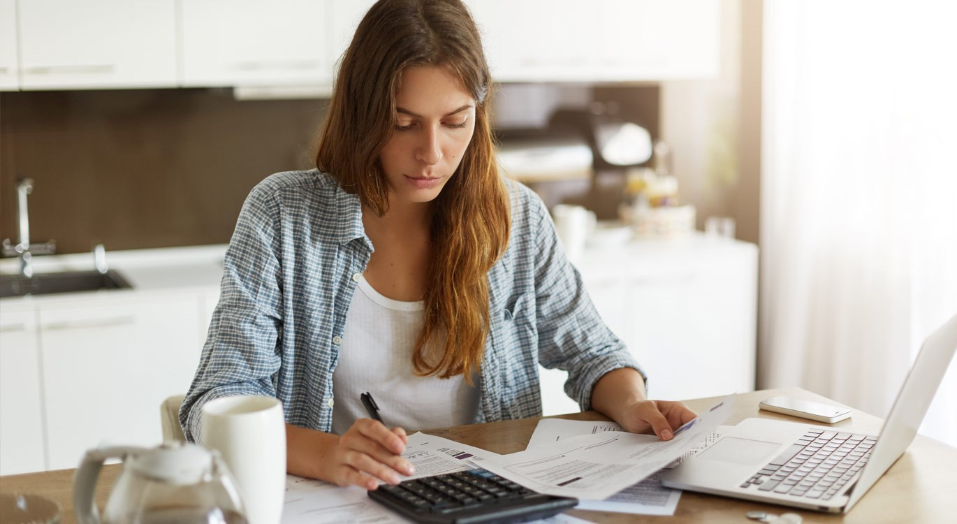 Woman sitting at a table at home, looking worried working on a calculator and laptop, surrounded by paperwork