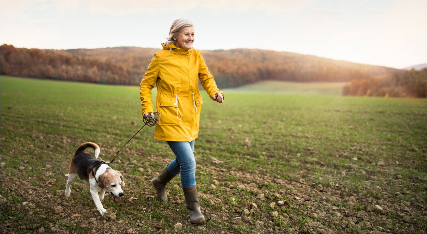 Happy middle-aged woman, walking her dog