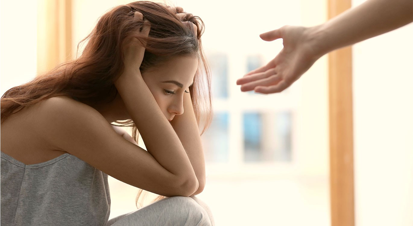 Mental health - Someone offering a hand to a depressed woman