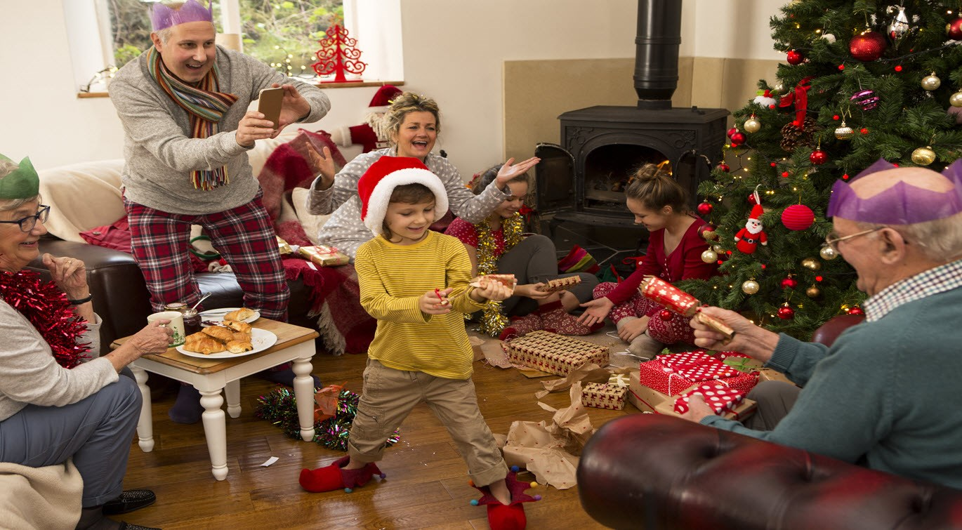 family-around-a-christmas-tree-opening-presents-and-pulling-crackers