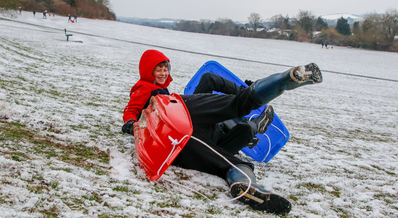 father and son falling off sledge and laughing
