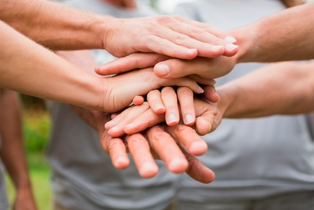 Team with hands together in the middle