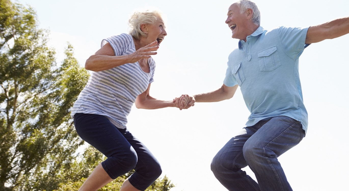 How to be happy in midlife - couple jumping on a trampoline