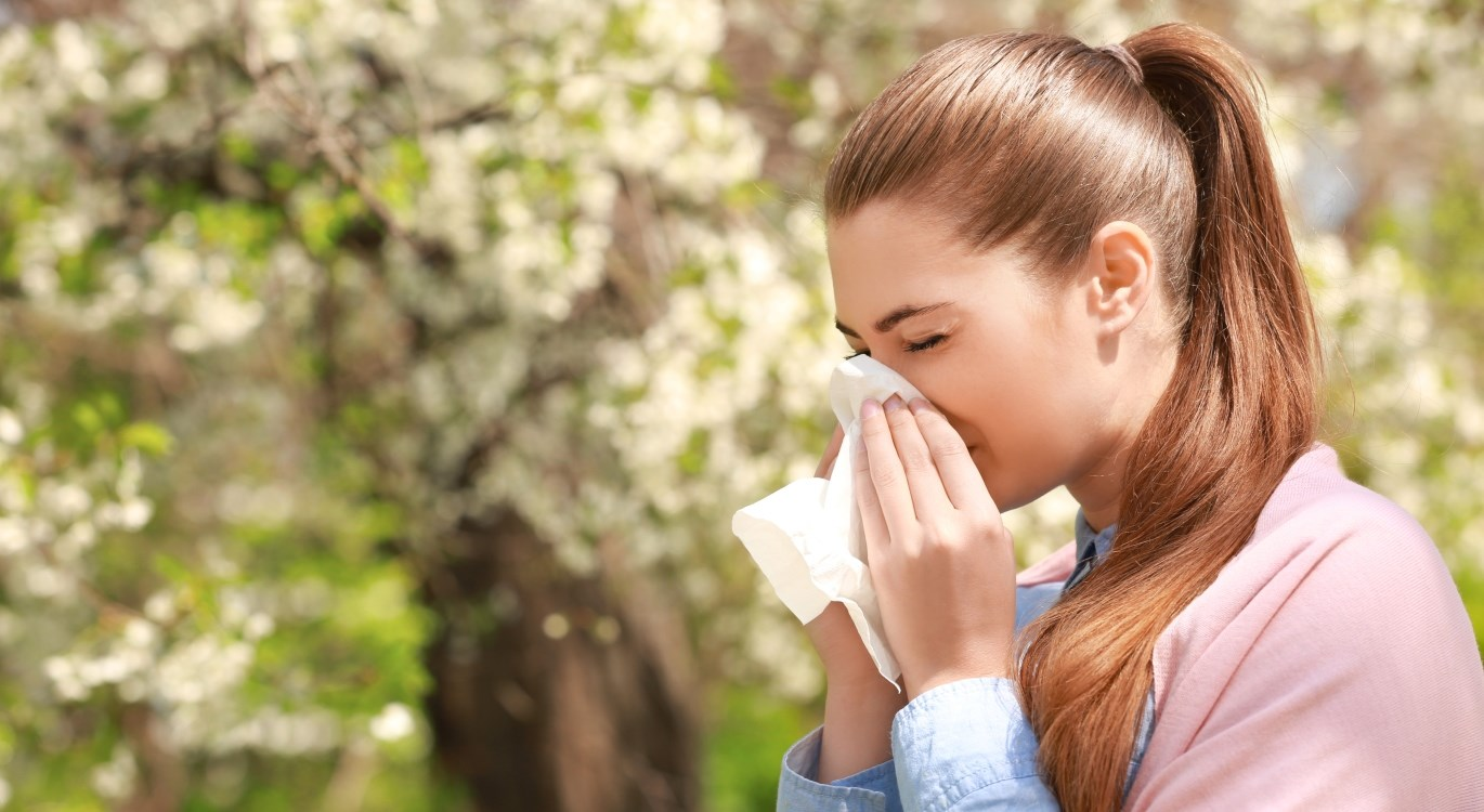 woman blowing her nose suffering from hay fever