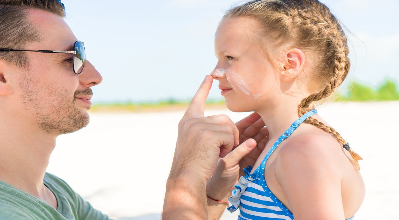 father_applying_face_cream_to_young_daughter