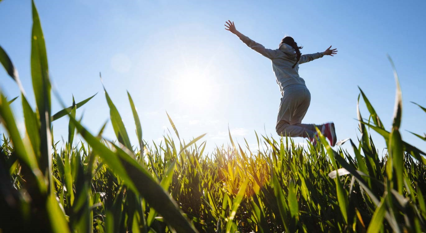Person jumping for joy in a field