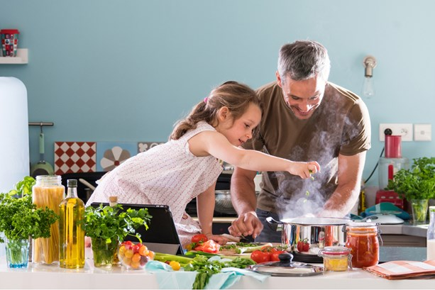 Father and daughter having fun cooking healthy food