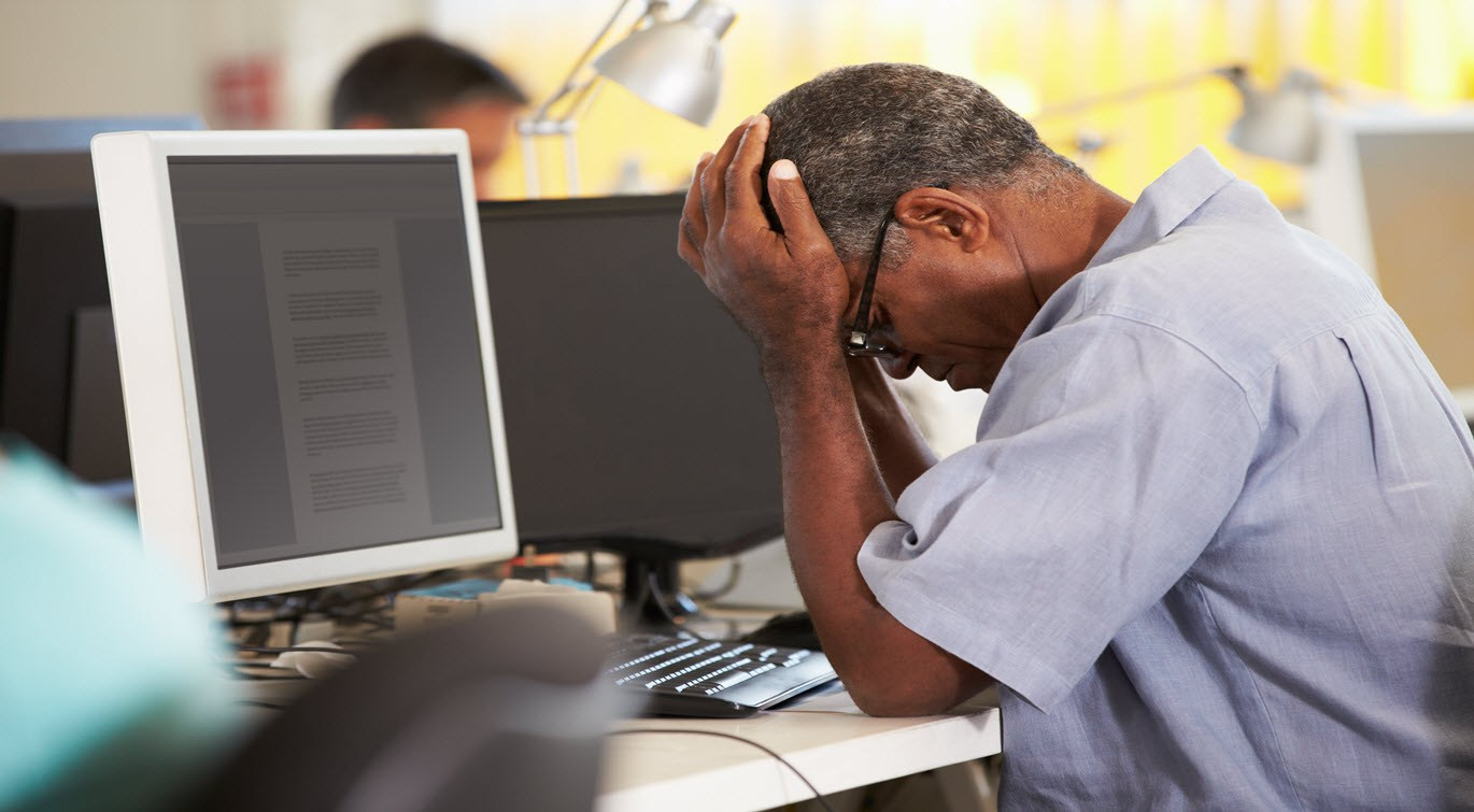 stressed-man-working-at-desk-in-busy-office