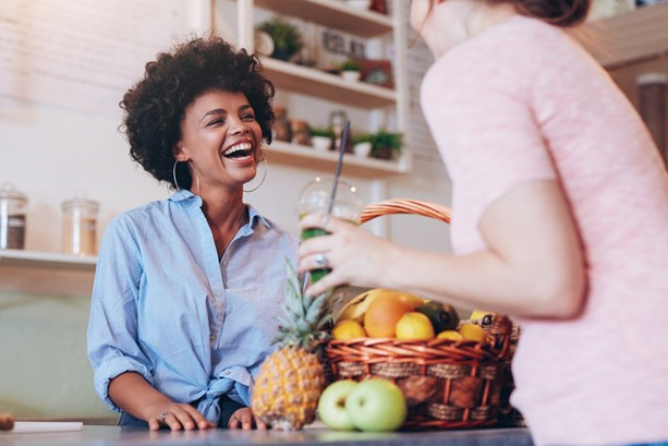 Female mployee buying juice from smiling woman at fresh juice bar