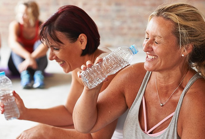 women laughing drinking water after exercise class