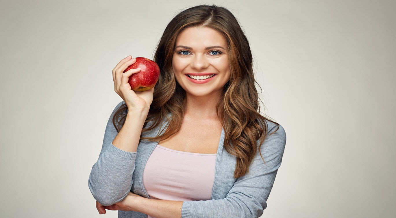 Woman smiling holding an apple