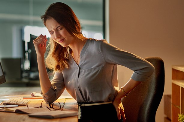 Woman at desk clutching her back in pain