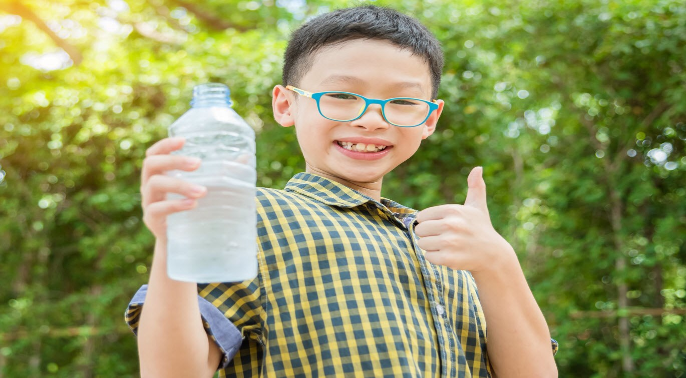 Young boy holding water bottle showing thumb up with smiles in park