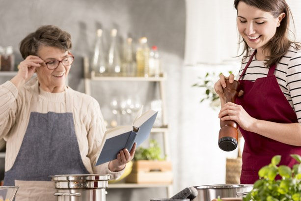 Two women from different generations cooking healthy food together