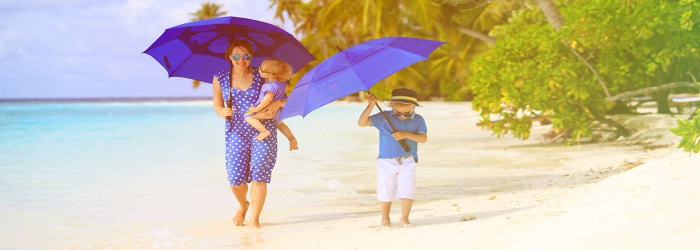 mother and two kids at beach with umbrellas to hide from sun