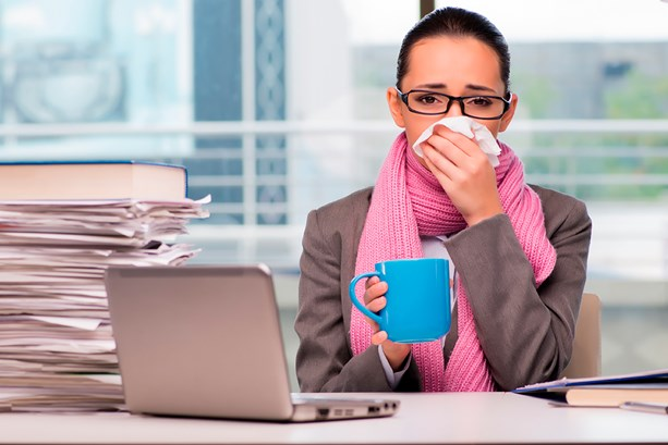 Woman with the flu sat at her desk at work